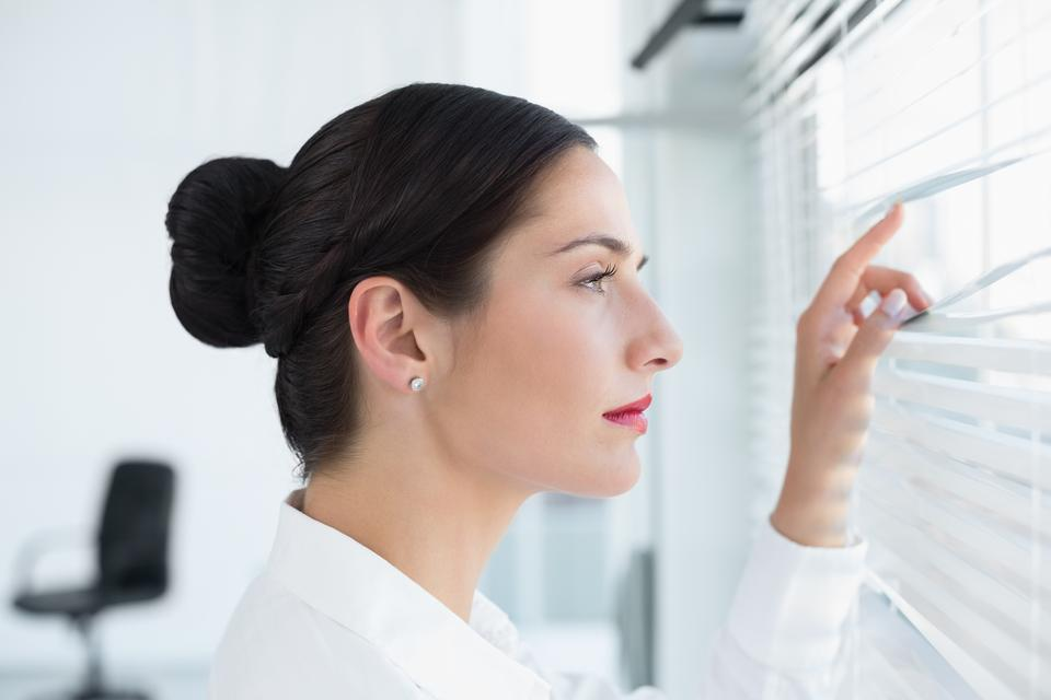 """""""Young business woman peeking through blinds at office"""" stock image"""