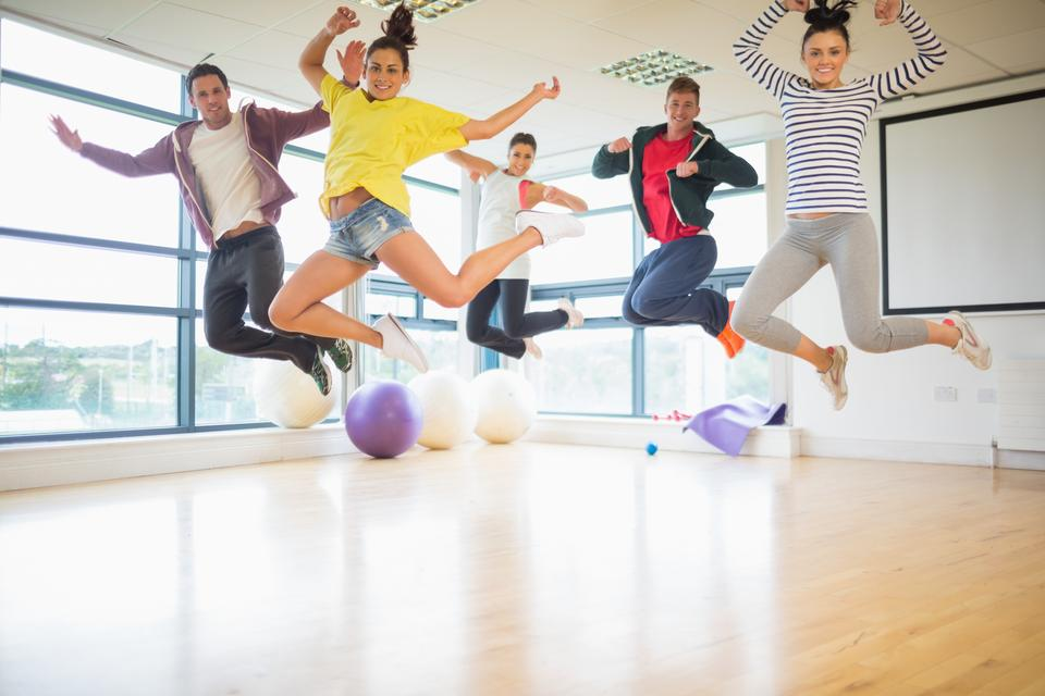 """Fit people jumping in exercise room"" stock image"