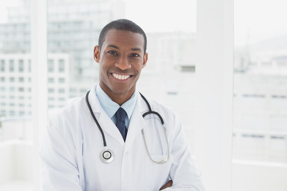 """""""Confident smiling male doctor in a medical office"""" stock image"""