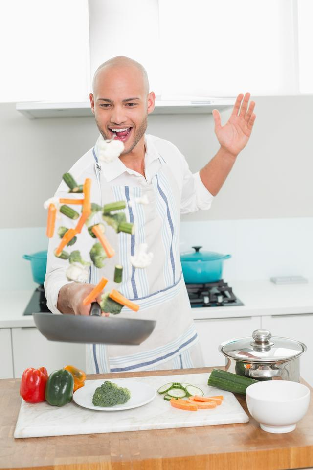 """Man tossing vegetables at the kitchen"" stock image"