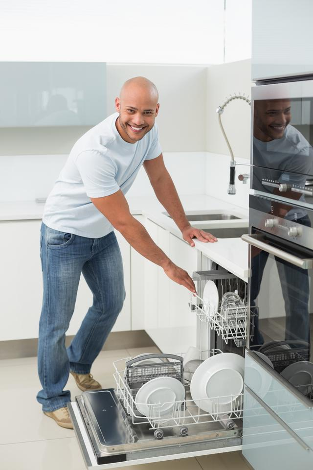 """""""Smiling young man using dish washer in kitchen"""" stock image"""