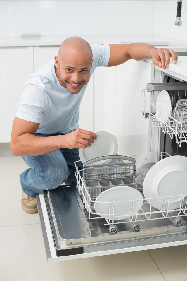 """""""Portrait of a smiling man using dish washer in kitchen"""" stock image"""