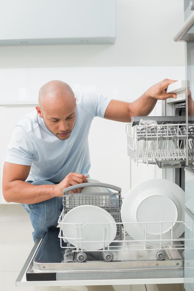 """""""Serious man using dish washer in kitchen"""" stock image"""