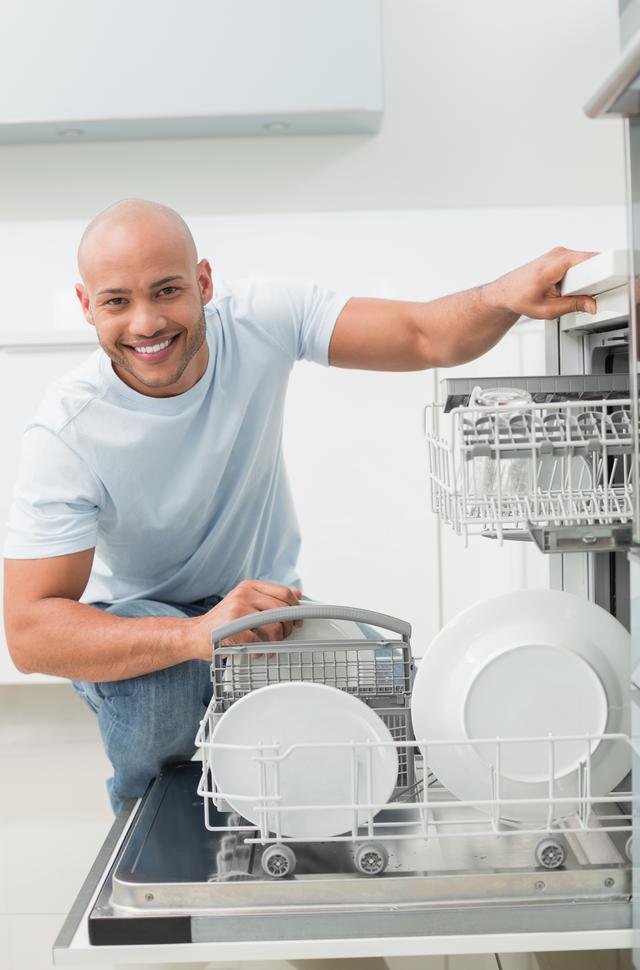 """""""Portrait of smiling man using dish washer in kitchen"""" stock image"""