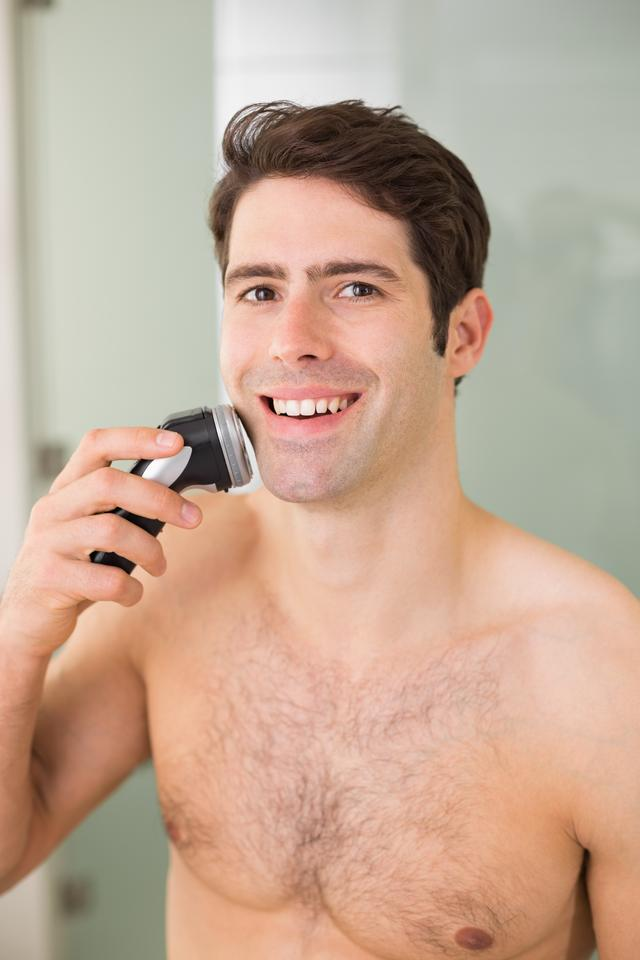 """""""Smiling handsome shirtless man shaving with electric razor"""" stock image"""