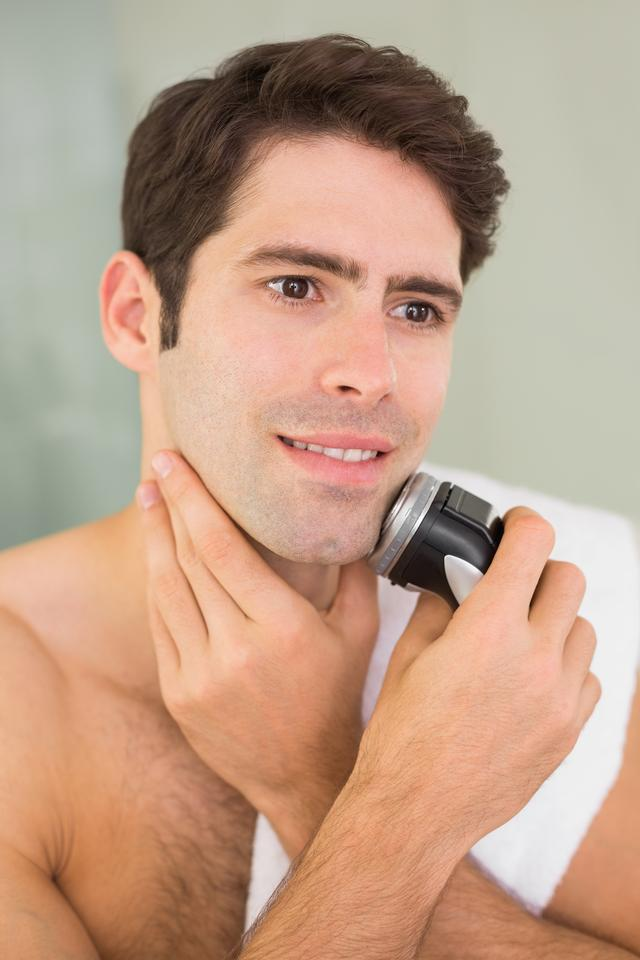 """""""Handsome shirtless man shaving with electric razor"""" stock image"""