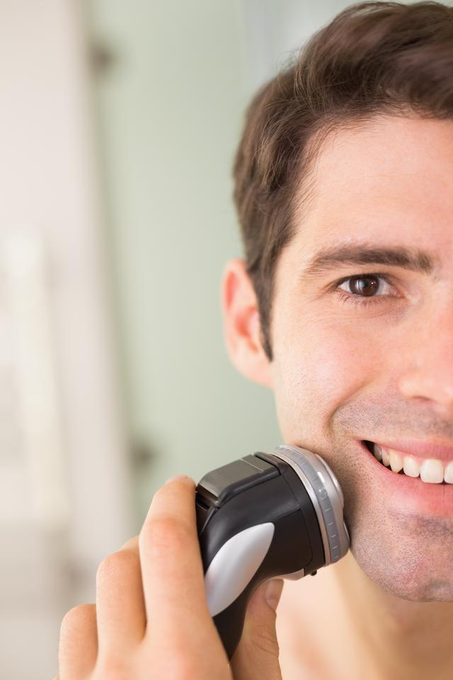 """""""Close up of smiling man shaving with electric razor"""" stock image"""
