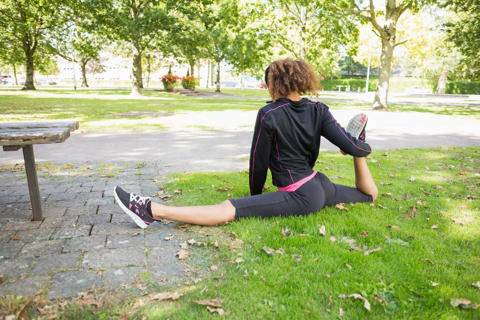 """""""Flexible young woman doing the splits exercise in park"""" stock image"""