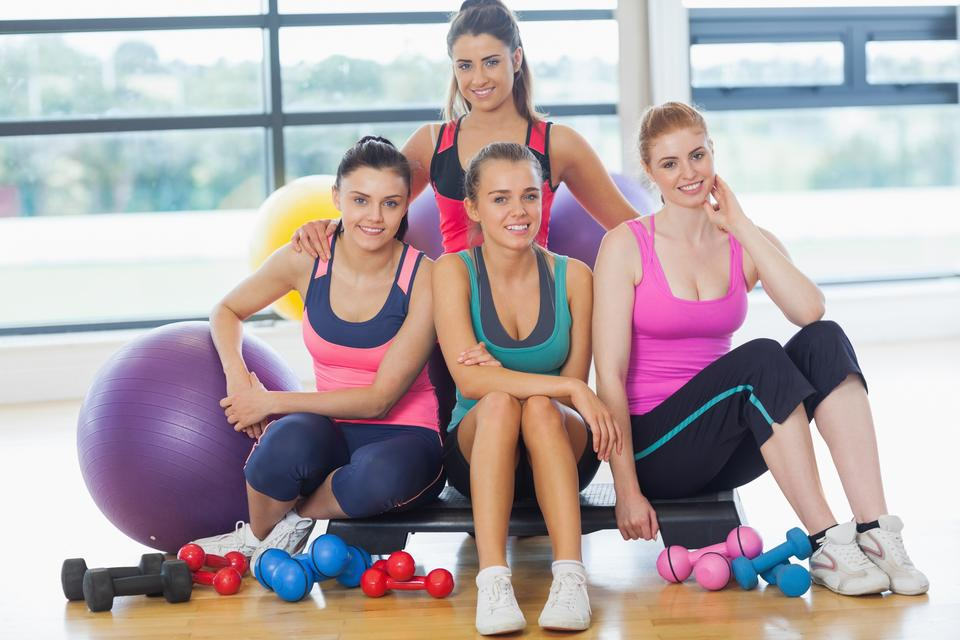 """Group of fitness class at a bright exercise room"" stock image"
