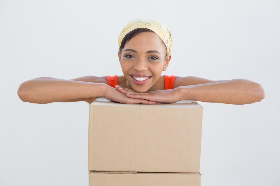 """""""Portrait of a smiling young woman with boxes"""" stock image"""