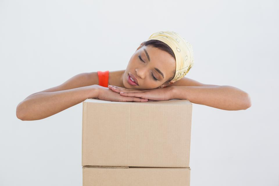 """""""Pretty young woman resting head over boxes"""" stock image"""