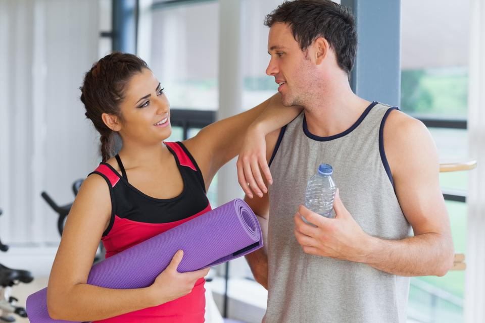 """Fit couple with water bottle and exercise mat in exercise room"" stock image"
