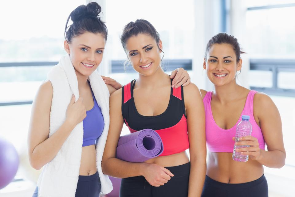 """Three fit young women smiling in exercise room"" stock image"