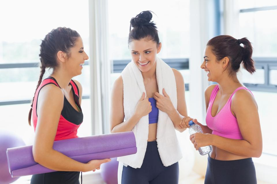 """Three fit young women chatting in exercise room"" stock image"
