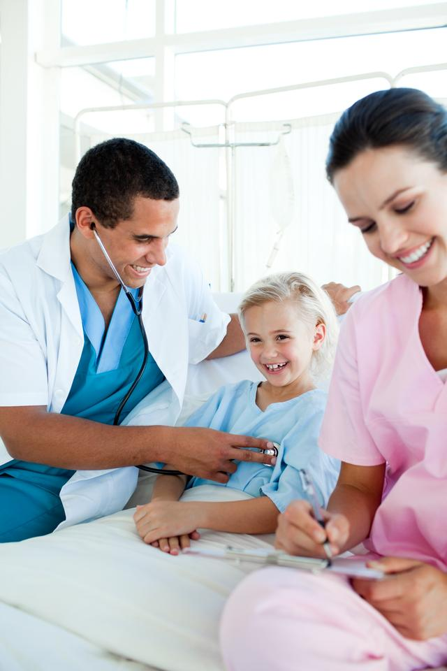 """Smiling blond girl at a checkup"" stock image"