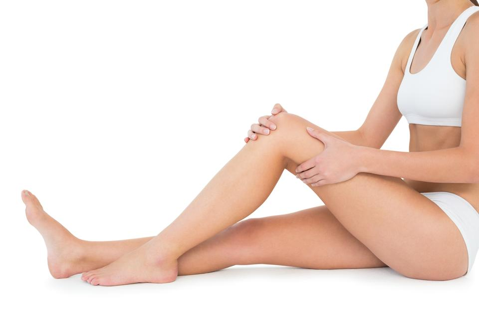 """""""Side view of a fit young woman with knee pain"""" stock image"""