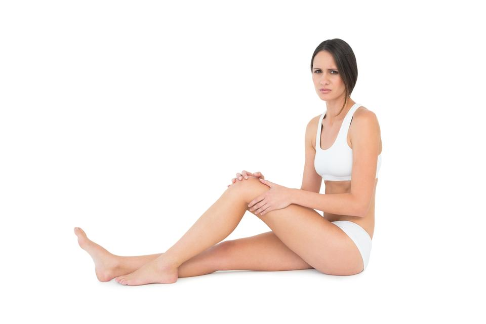 """""""Side view portrait of a fit woman with knee pain"""" stock image"""