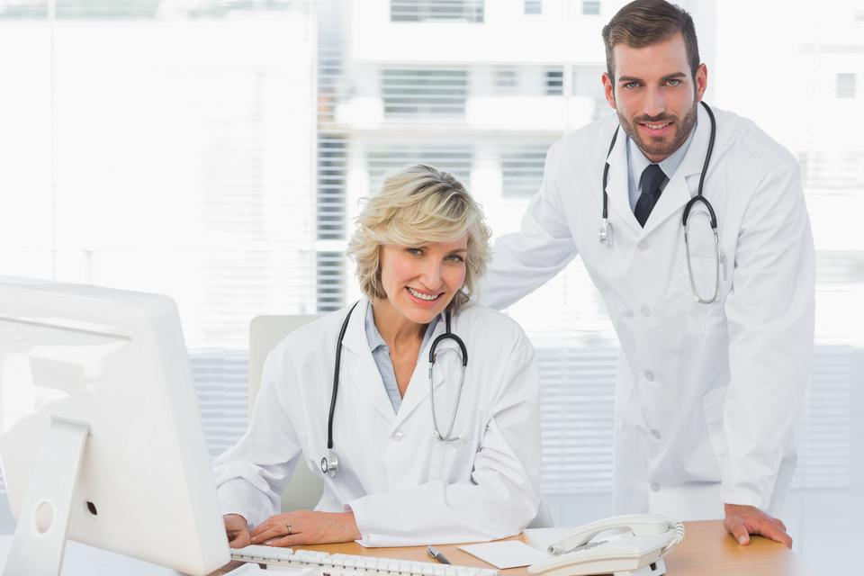 """""""Smiling doctors with computer at medical office"""" stock image"""