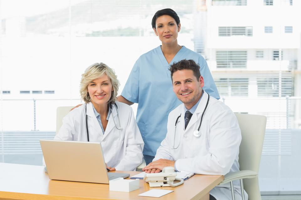 """""""Smiling doctors with laptop at medical office"""" stock image"""