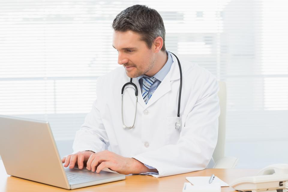 """""""Doctor working on laptop at medical office"""" stock image"""