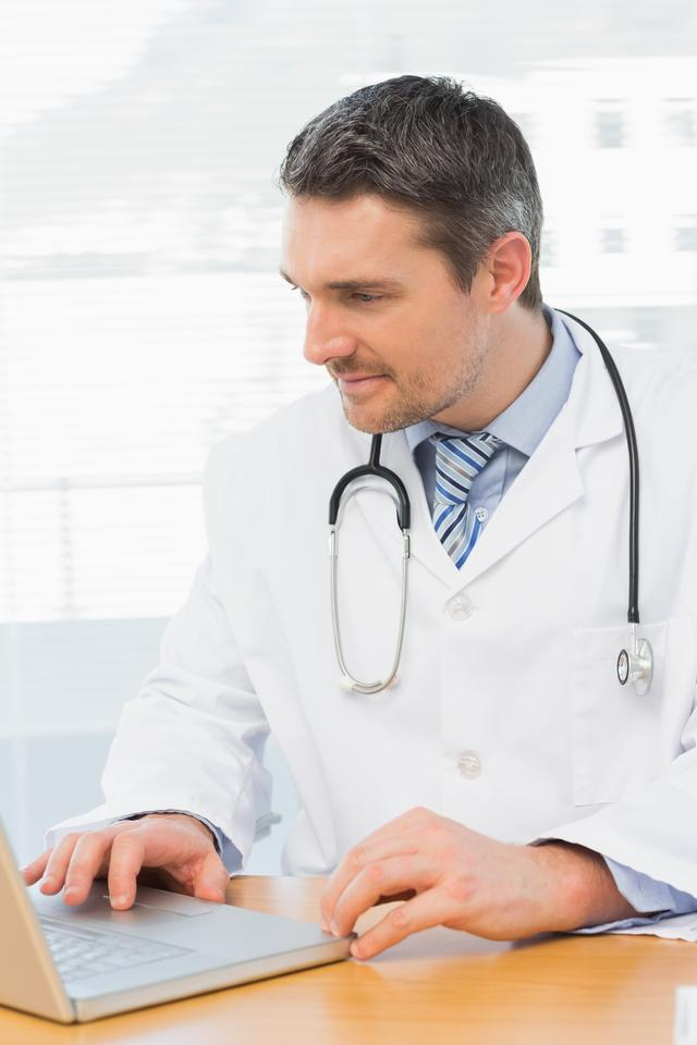 """""""Doctor working on laptop in medical office"""" stock image"""