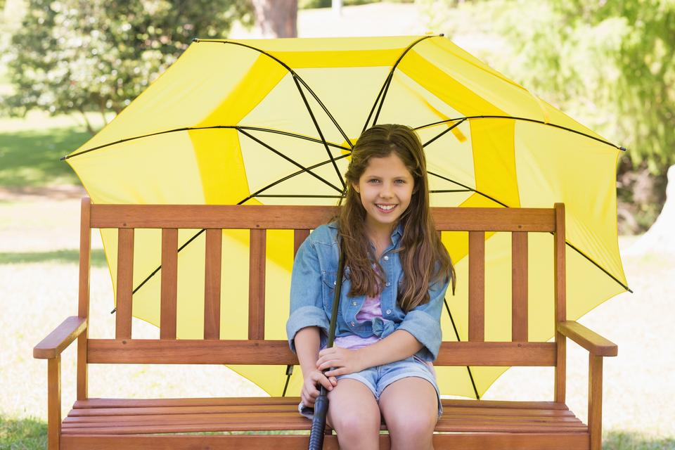 """Girl sitting on park bench with an umbrella"" stock image"
