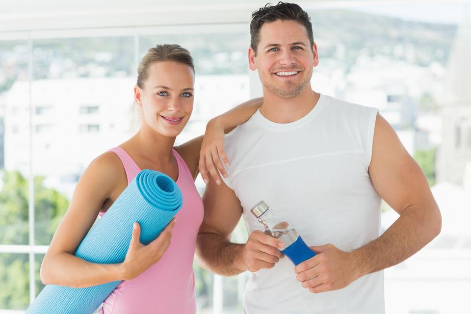 """Fit couple holding water bottle and exercise mat in exercise room"" stock image"