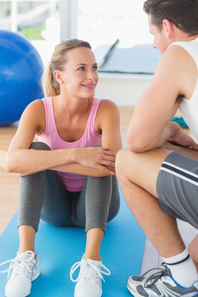 """Smiling fit couple chatting in exercise room"" stock image"