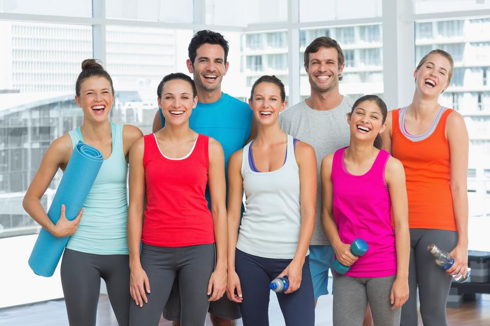 """Portrait of fit people smiling in exercise room"" stock image"
