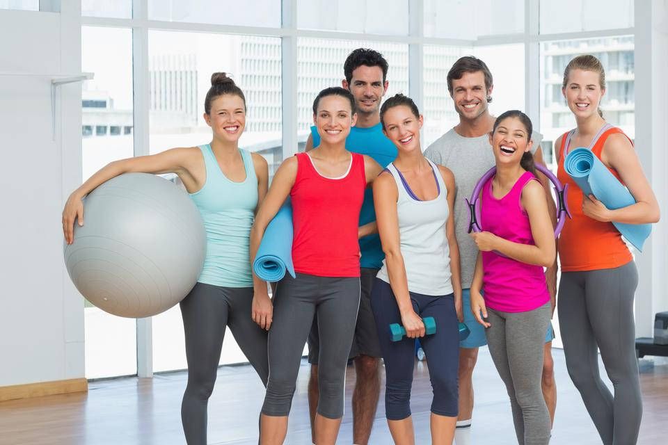 """Fit people smiling in a bright exercise room"" stock image"