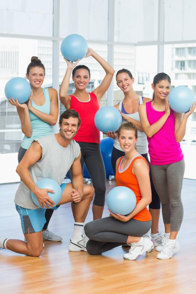 """Fit young people with balls in exercise room"" stock image"