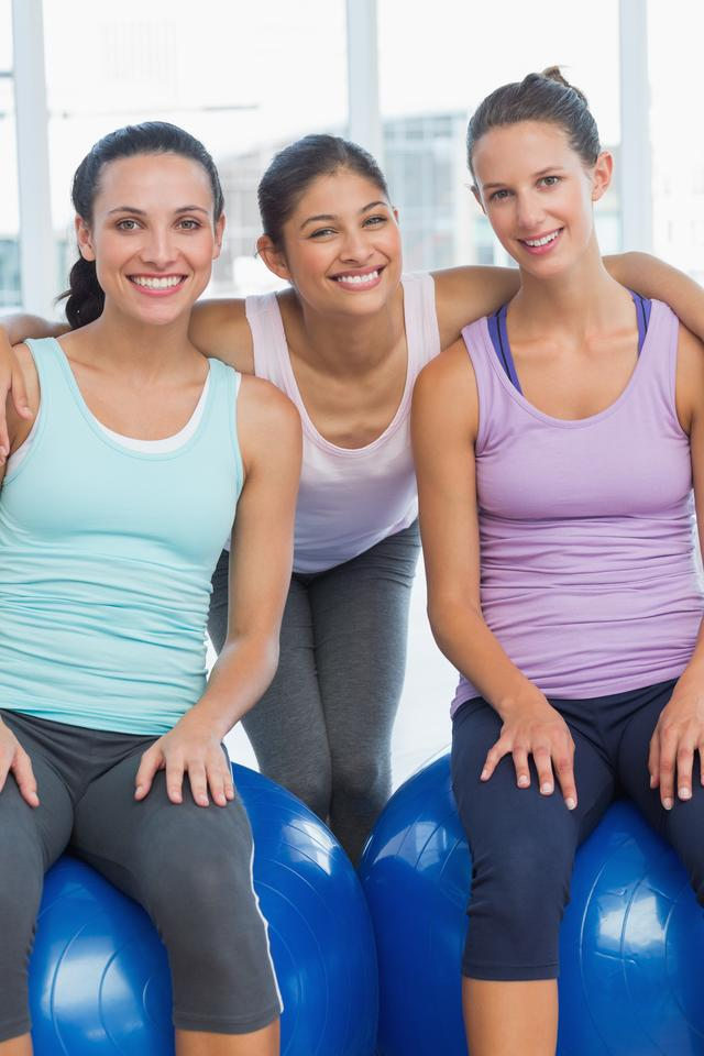 """Fit young women smiling in exercise room"" stock image"