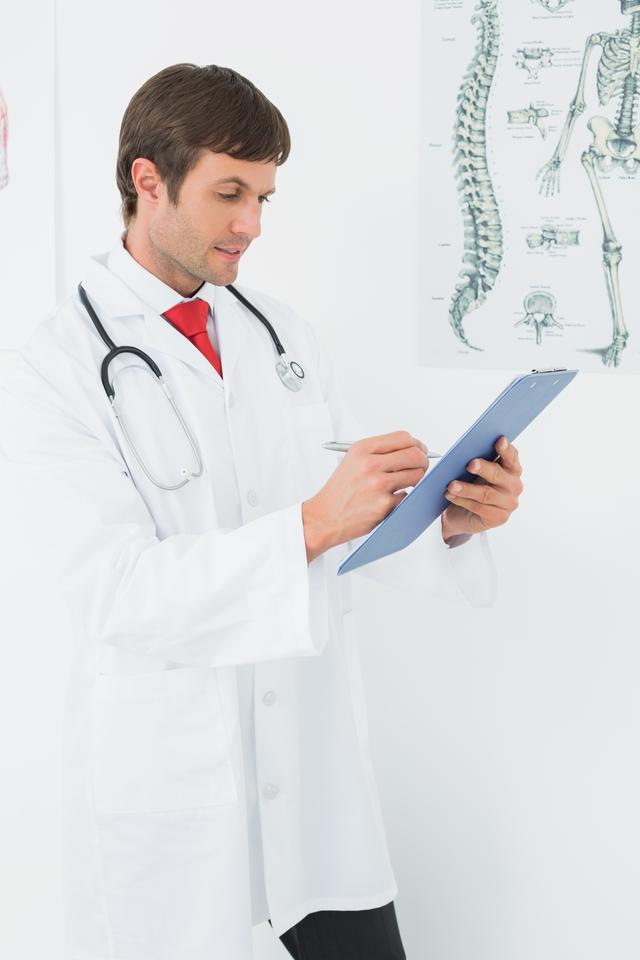"""""""Doctor writing reports in the medical office"""" stock image"""