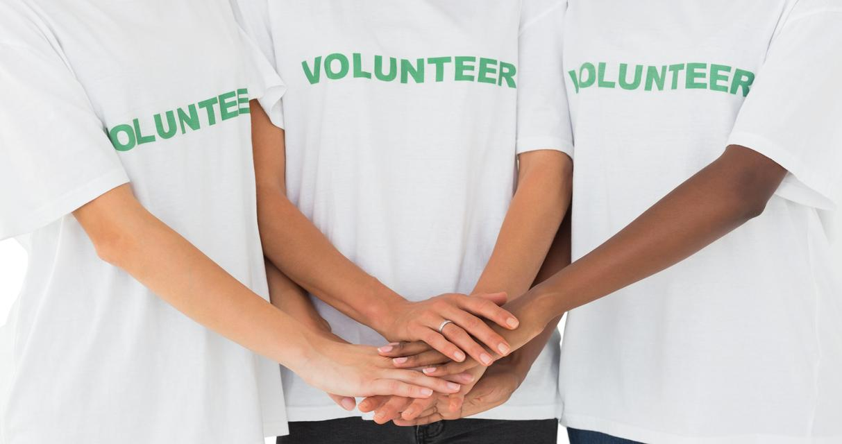 """Team of volunteers putting hands together"" stock image"