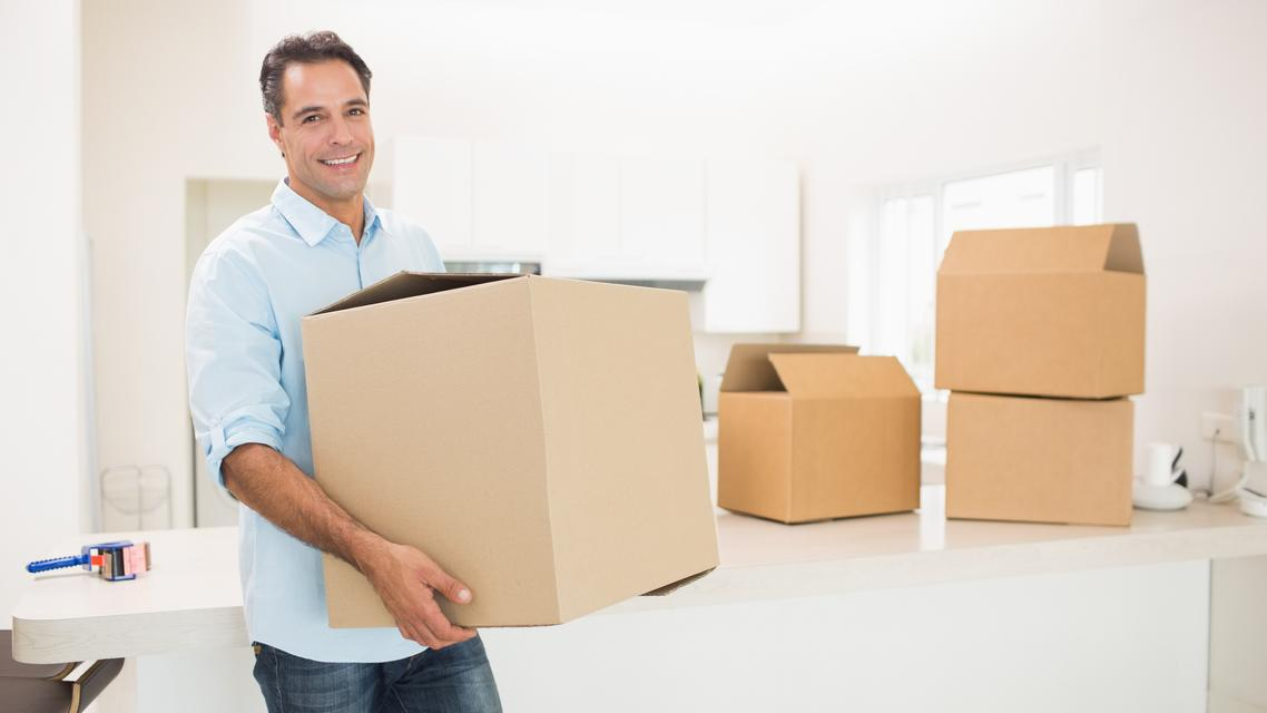 """""""Man carrying boxes in a new house"""" stock image"""