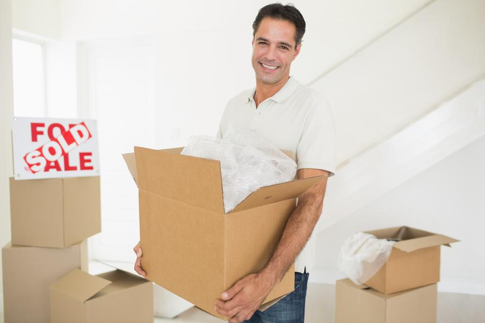 """""""Smiling man carrying boxes in a new house"""" stock image"""