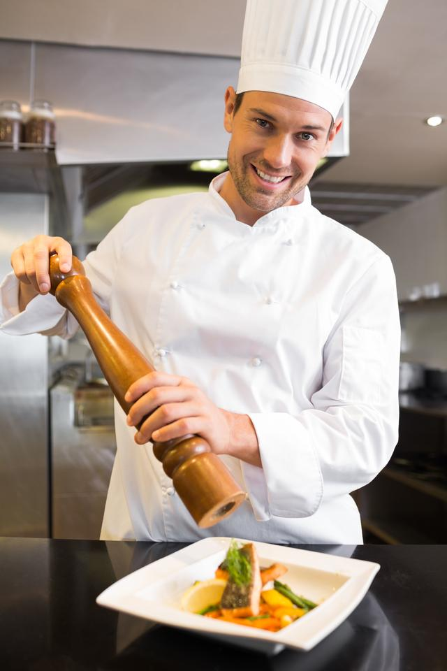 """""""Smiling male cook grinding pepper on food in kitchen"""" stock image"""