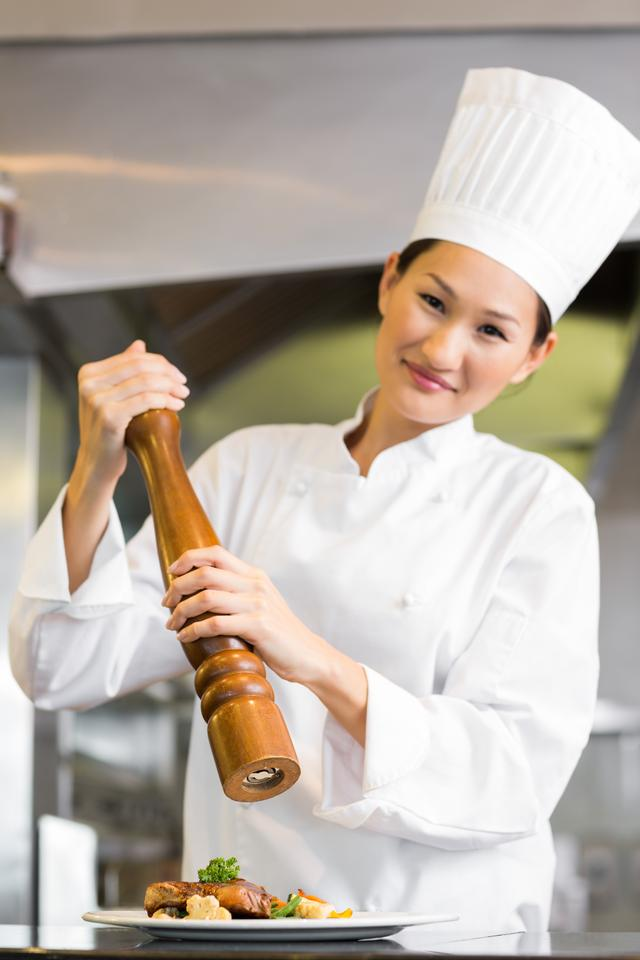 """""""Smiling female cook grinding pepper on food in kitchen"""" stock image"""