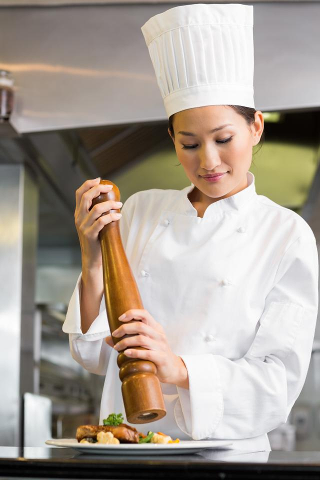 """""""Female cook grinding pepper on food in kitchen"""" stock image"""
