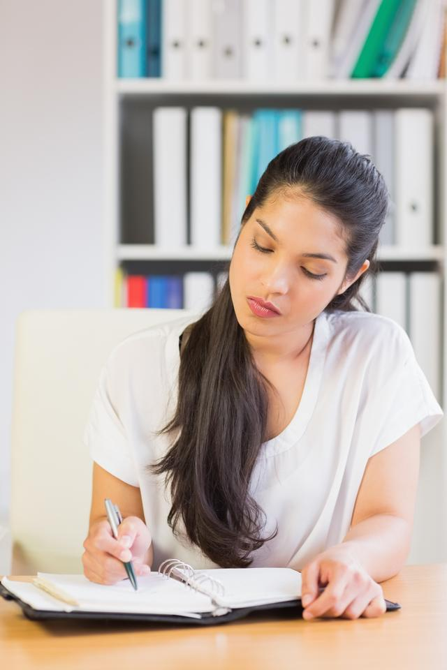 """Businesswoman writing notes in diary"" stock image"