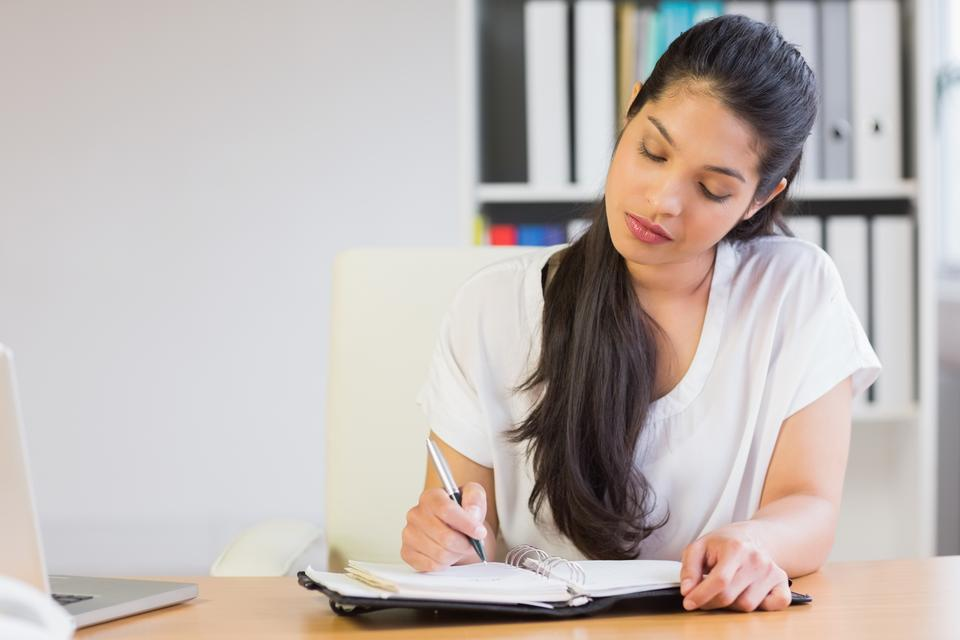 """Young businesswoman writing in diary"" stock image"