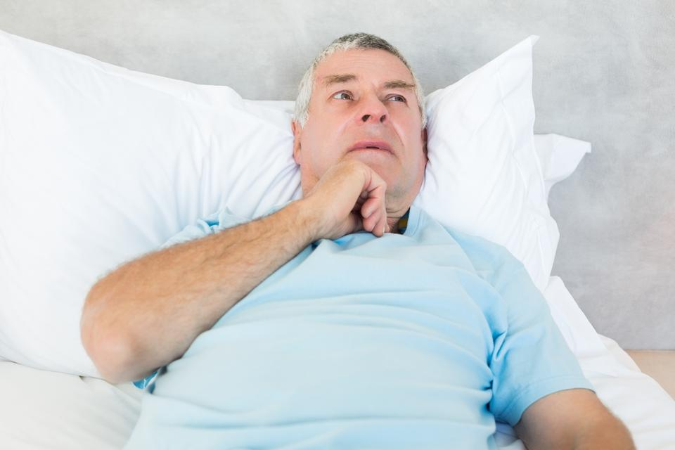 """""""Thoughtful senior man lying in bed"""" stock image"""