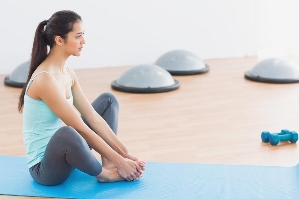 """Fit woman doing butterfly stretch in exercise room"" stock image"