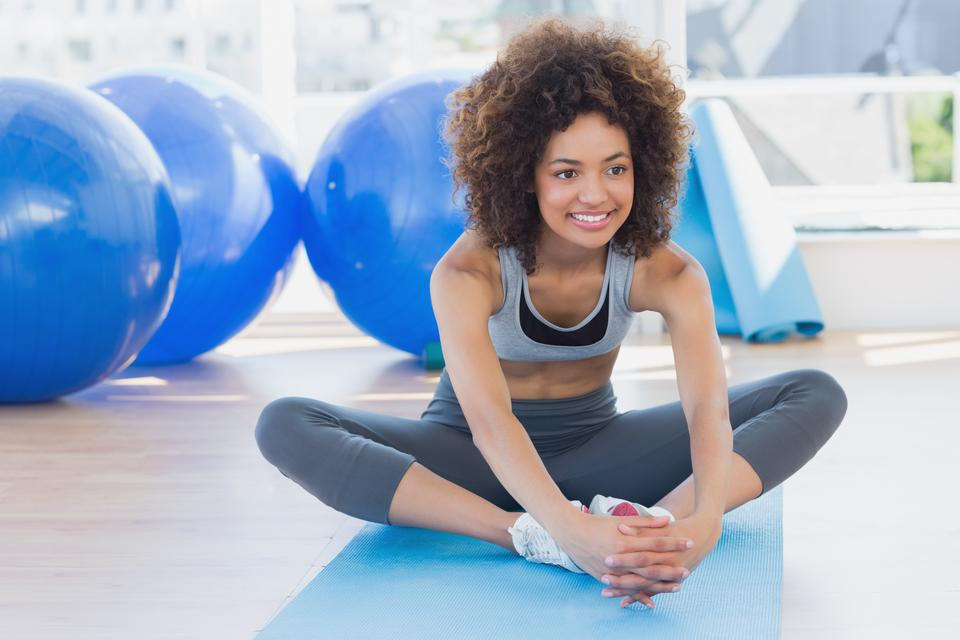 """Fit woman doing the butterfly stretch in exercise room"" stock image"