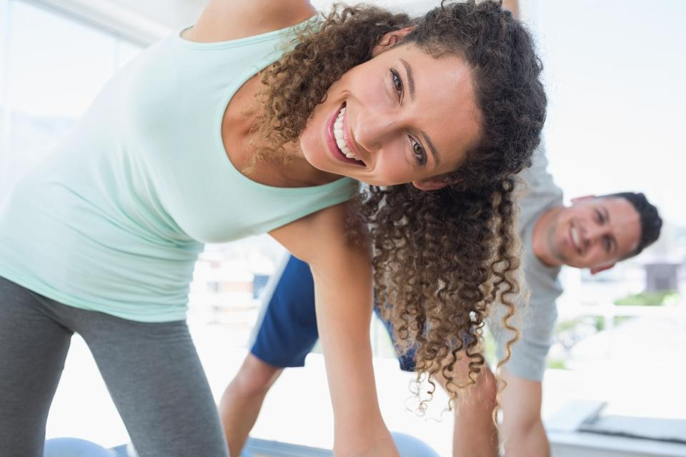 """Woman stretching in exercise room"" stock image"