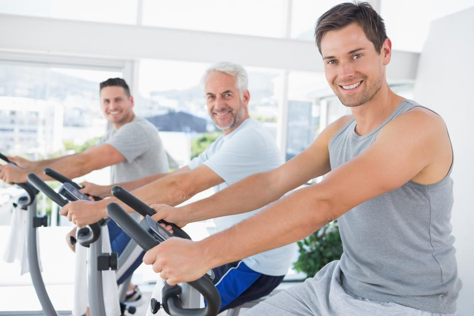 """Men on exercise bikes"" stock image"