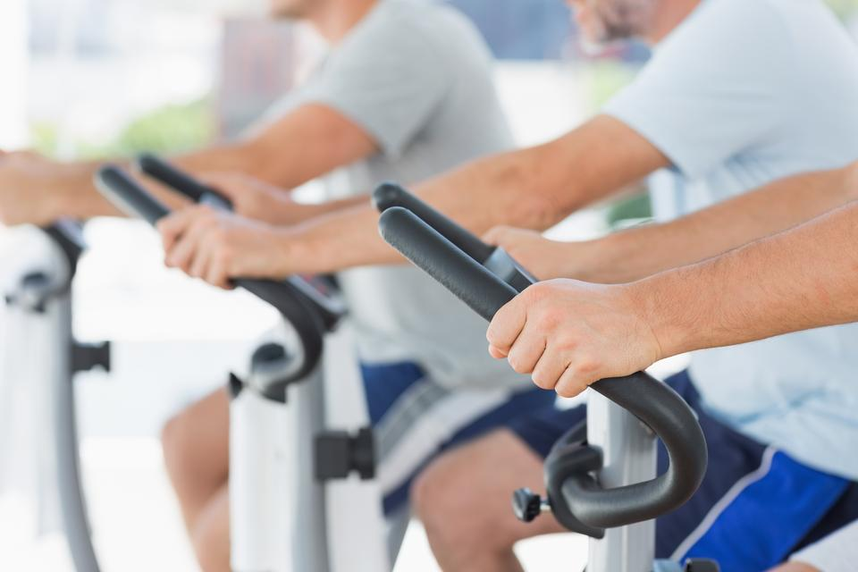 """Men using exercise bikes"" stock image"