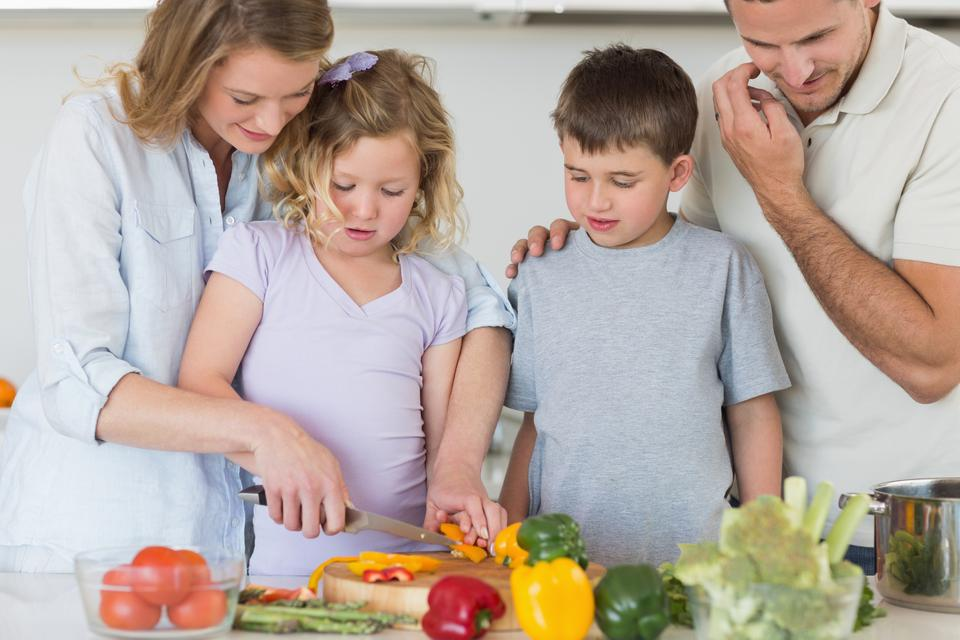 """""""Family chopping vegetables in kitchen"""" stock image"""