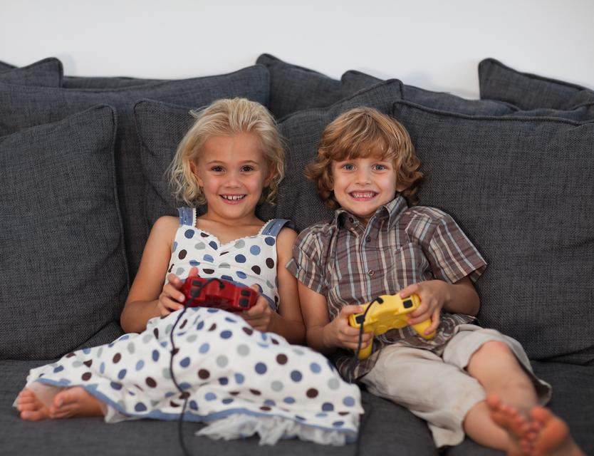 """Cheerful children playing video games at home"" stock image"