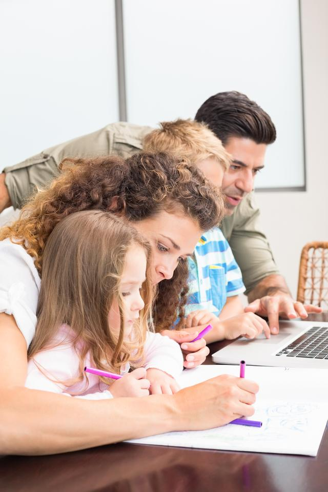 """""""Attractive parents colouring and using laptop with their children"""" stock image"""